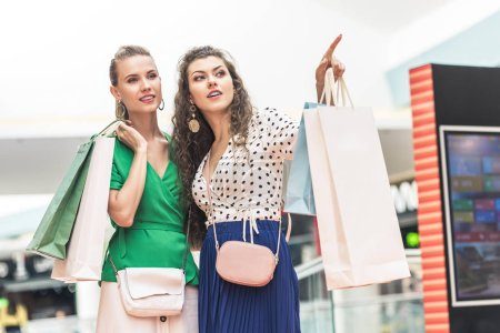 stylish young women holding paper bags and looking away in shopping mall