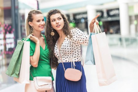 beautiful stylish girls holding paper bags and looking away in shopping mall