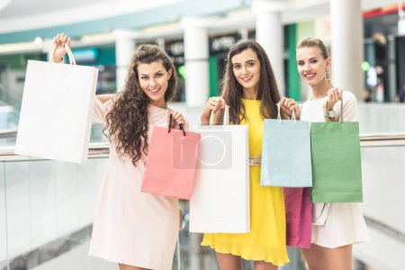 three beautiful happy girls holding shopping bags and smiling at camera in mall
