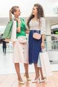 beautiful stylish young women holding shopping bags and smiling each other in mall