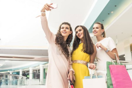 Photo for Low angle view of happy stylish girls holding paper bags and taking selfie with smartphone in shopping mall - Royalty Free Image