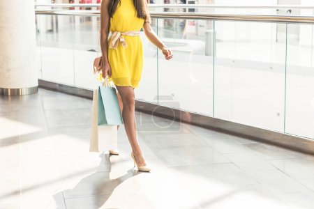 cropped shot of stylish girl in yellow dress holding paper bags and walking in shopping mall