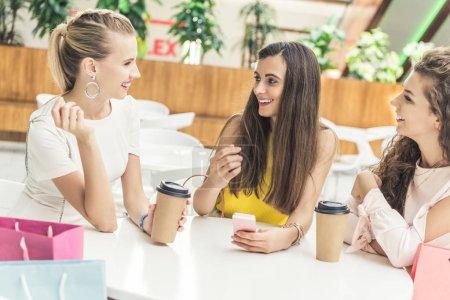 Photo pour Belles filles souriantes à l'aide de smartphone et de boire du café dans des tasses en papier au centre commercial café - image libre de droit
