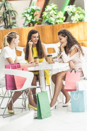 beautiful smiling young women drinking coffee from paper cups and talking while sitting in cafe at shopping mall