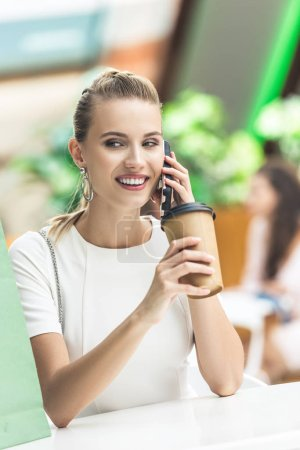 beautiful smiling girl holding disposable coffee cup and talking by smartphone while sitting in cafe at shopping mall