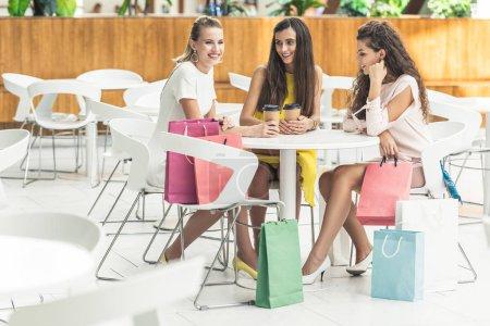 Photo pour Belles filles souriantes tenant des gobelets en papier et parler tout en étant assis au centre commercial café - image libre de droit