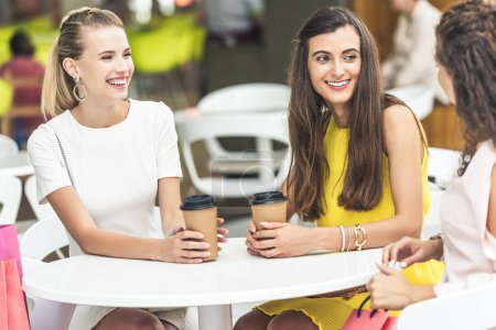 beautiful smiling young women holding paper cups and talking while sitting in cafe at shopping mall