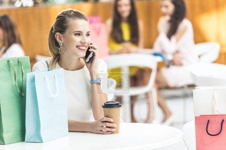 Photo pour Belle jeune femme souriante parler de smartphone et la tenue de gobelet en papier tout en étant assis au centre commercial café - image libre de droit