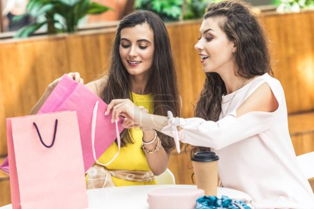 smiling young women looking into shopping bag while sitting at table in shopping mall