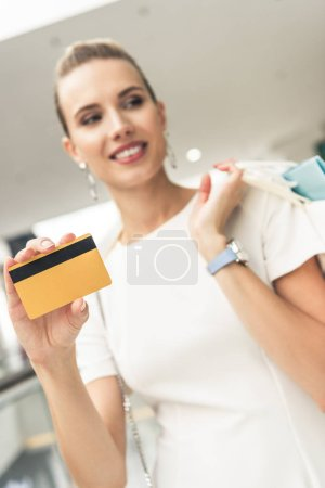 close-up view of smiling young woman holding credit card and shopping bags