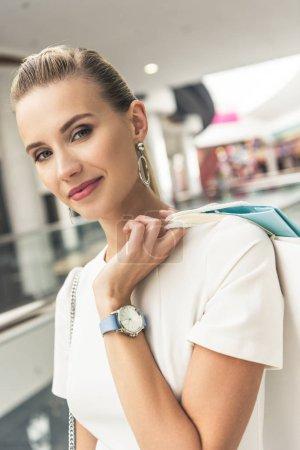 Photo pour Belle jeune femme tenant des sacs en papier et souriant à la caméra dans le centre commercial - image libre de droit
