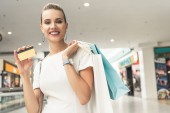 beautiful young woman holding paper bags and credit card, smiling at camera in shopping mall
