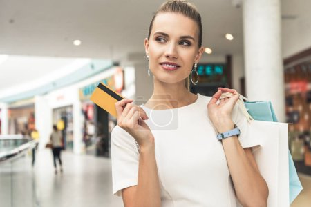 Photo for Beautiful smiling young woman holding paper bags and credit card in shopping mall - Royalty Free Image