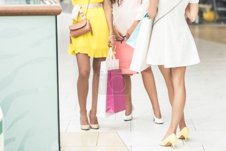 cropped shot of girls in high heeled shoes holding paper bags in shopping mall