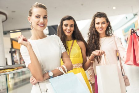 stylish young women holding credit card and paper bags, smiling at camera in shopping mall