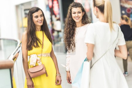 fashionable young women smiling each other in shopping mall