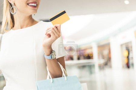 Photo pour Plan recadré d'une jeune femme souriante tenant une carte de crédit dans un centre commercial - image libre de droit