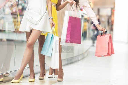 low section of stylish young women holding shopping bags