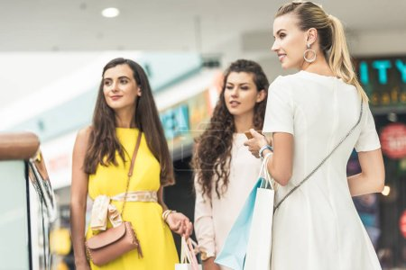 beautiful fashionable young women holding paper bags and looking away at shopping mall