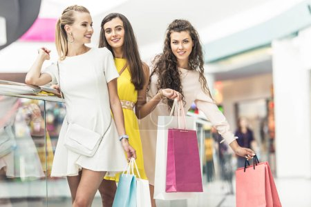 beautiful stylish young women holding shopping bags and smiling at camera