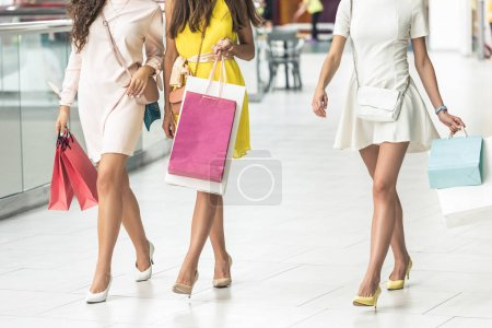 cropped shot of stylish young women with paper bags walking in shopping mall