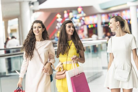 smiling stylish young women holding paper bags and walking in shopping mall