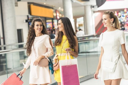 beautiful smiling young women holding paper bags and walking in shopping mall