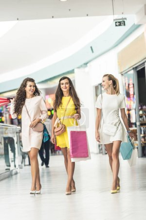 three stylish smiling girls holding paper bags and walking in shopping mall