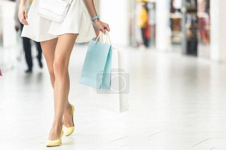 low section of stylish girl holding paper bags and walking in shopping mall