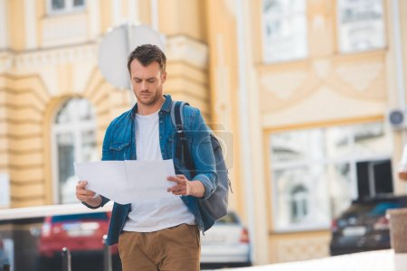 Photo for Portrait of focused traveler with backpack and map on city street - Royalty Free Image