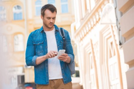 Photo for Portrait of focused man in denim shirt using smartphone on street - Royalty Free Image