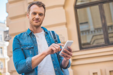 Photo for Handsome young man using smartphone and looking at camera on street - Royalty Free Image