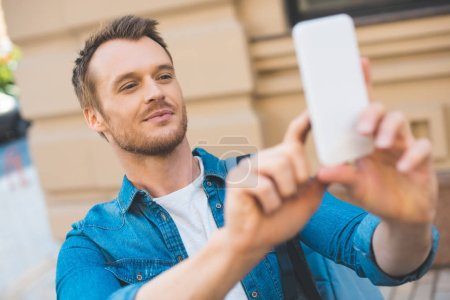 close-up portrait of handsome young tourist with backpack taking photo with smartphone on street