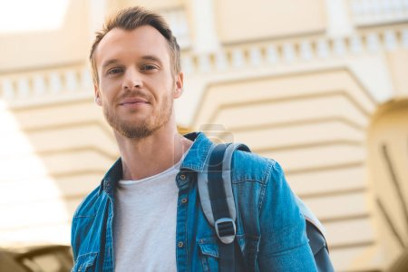 Photo for Attractive young man with backpack looking at camera on street - Royalty Free Image