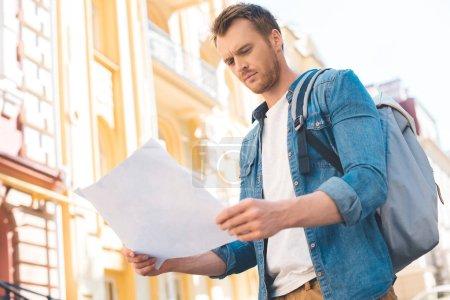 Photo pour Beau jeune touriste avec sac à dos, regardant la carte sur la rue - image libre de droit