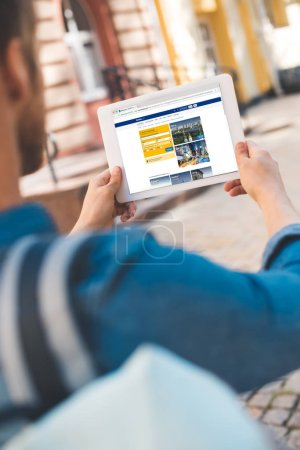 cropped shot of young man using tablet with booking website on screen while walking by street