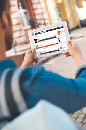 cropped shot of young man using tablet with soundcloud website on screen while walking by street