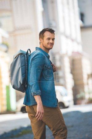 Photo pour Séduisante jeune touriste avec sac à dos à pied par la rue et de regarder la caméra - image libre de droit