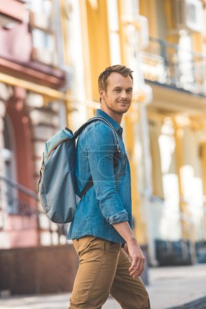 Photo for Attractive young traveller with backpack walking by street and looking at camera - Royalty Free Image