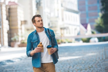 handsome young man with backpack, coffee to go and croissant walking by street and looking away