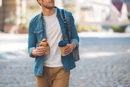 cropped shot of happy man with backpack, coffee to go and croissant walking by street and looking away