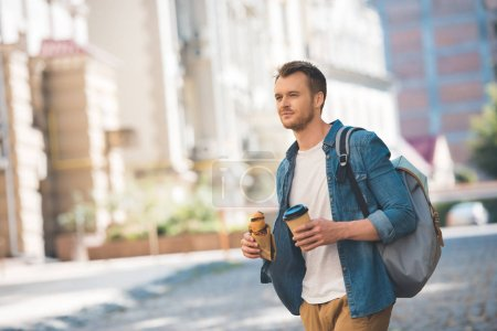 Photo for Handsome young man with backpack, coffee to go and croissant walking by street and looking at camera - Royalty Free Image