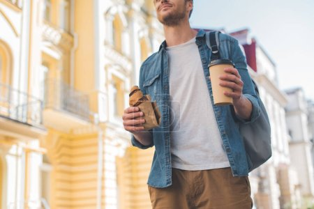 cropped shot of happy man with backpack, coffee to go and croissant walking by street