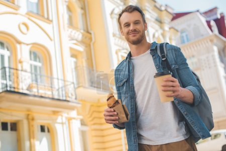 bottom view of handsome young man with backpack, coffee to go and croissant walking by street and looking at camera