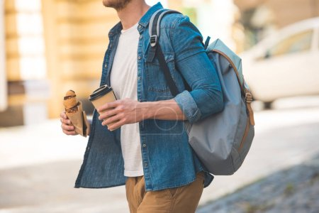 cropped shot of man with backpack, coffee to go and croissant walking by street
