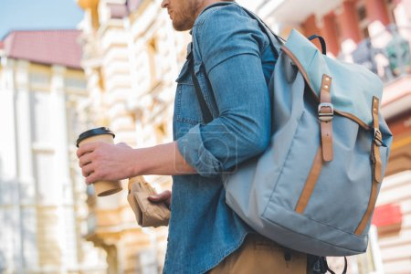 cropped shot of young man with backpack, coffee to go and croissant walking by street