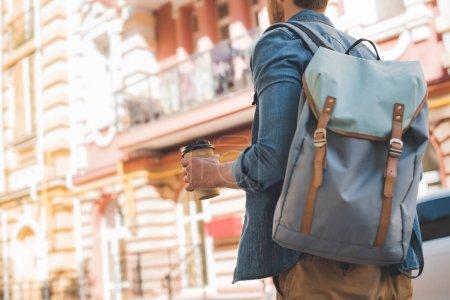 Photo pour Recadrée tir du jeune homme avec sac à dos et café pour aller à pied par la rue - image libre de droit