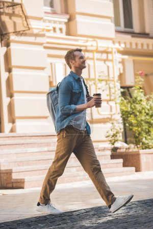 casual young man with coffee to go and backpack walking by street and looking away