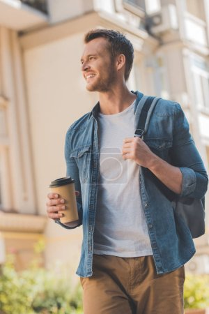 bottom view of happy young man with coffee to go and backpack walking on street and looking away