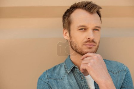 gros plan portrait de gentil jeune homme regardant la caméra en face de mur